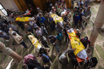 Palestinian mourners carry out the bodies of Rasmi Abu Malhous and seven members of his family who were killed in overnight Israeli missile strikes that targeted their house, during their funeral at a mosque in Deir al-Balah, central Gaza Strip, Thursday, Nov. 14, 2019. (AP Photo/Khalil Hamra)