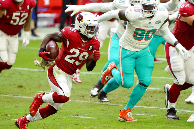 Arizona Cardinals running back Chase Edmonds (29) runs the ball as Miami Dolphins defensive end Shaq Lawson (90) pursues during the first half of an NFL football game, Sunday, Nov. 8, 2020, in Glendale, Ariz. (AP Photo/Rick Scuteri)