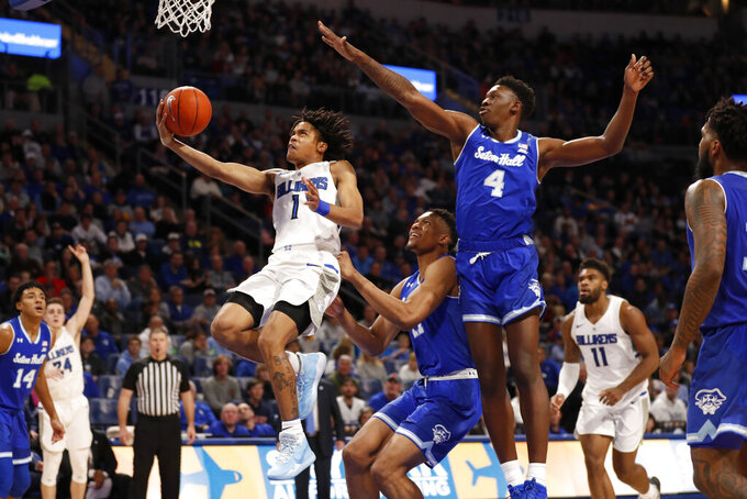 Saint Louis' Yuri Collins (1) heads to the basket past Seton Hall's Ike Obiagu and Tyrese Samuel (4) during the second half of an NCAA college basketball game Sunday, Nov. 17, 2019, in St. Louis. (AP Photo/Jeff Roberson)