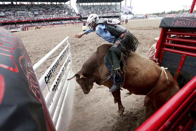 FILE - In this July 22, 2019, file photo, J.T. Moore, of Alvin, Texas, competes in bull riding at Frontier Park Arena in Cheyenne, Wy., during the Cheyenne Frontier Days event. The Cheyenne Frontier Days has been held for 123 straight years. The organizers are holding out hope the event scheduled for July won't be interrupted by the new coronavirus. It's a financial bonanza for the capital city situated in the southeast corner of Wyoming. The 10-day event drew more than 262,000 spectators last year. (Michael Cummo/Wyoming Tribune Eagle via AP, File)