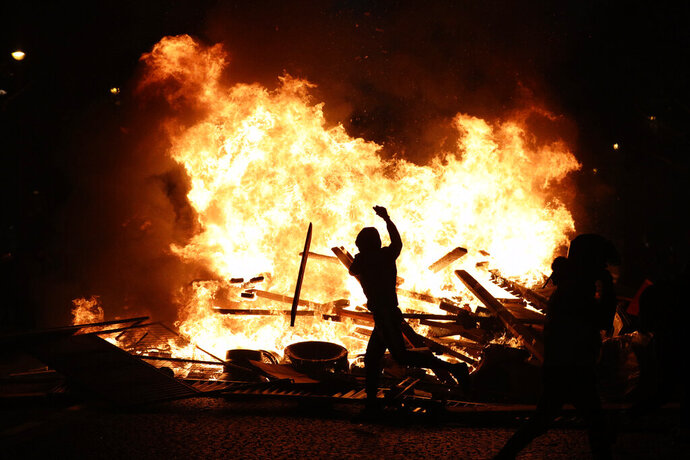 FILE - In this Nov. 24, 2018, file photo, a demonstrator throws debris at a burning barricade while protesting with others against the rising of the fuel taxes on the famed Champs Elysees avenue, in Paris. The offer by Italy's 5-Star Movement to share its web platform with France's