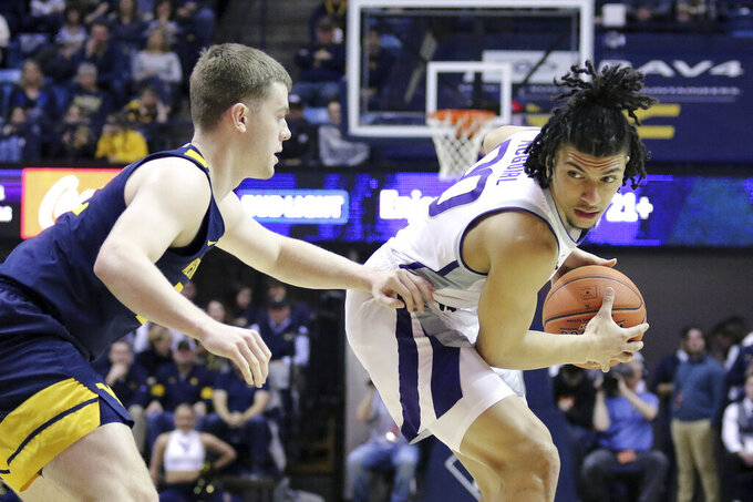 Kansas State guard Mike McGuirl, right, goes to pass the ball as he is defended by West Virginia guard Sean McNeil (22) during the first half of an NCAA college basketball game Saturday, Feb. 1, 2020, in Morgantown, W.Va. (AP Photo/Kathleen Batten)