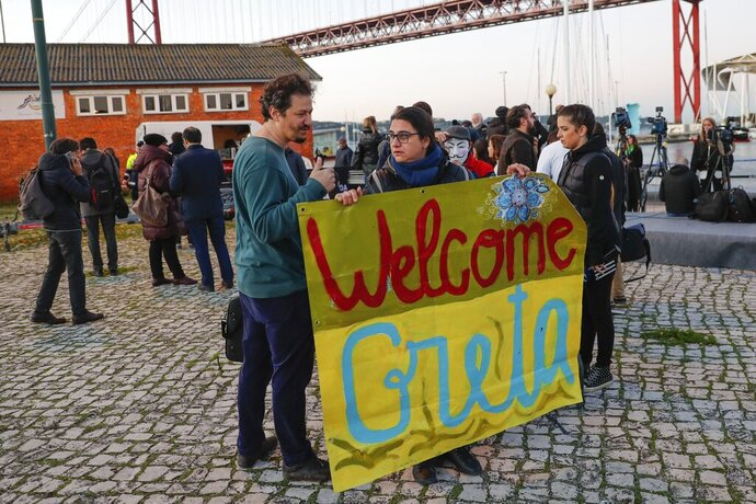 Climate activists wait for the arrival of Greta Thunberg in Lisbon, Tuesday, Dec 3, 2019. Climate activist Greta Thunberg has arrived by catamaran in the port of Lisbon after a three-week voyage across the Atlantic Ocean from the United States. The Swedish teen sailed to the Portuguese capital before heading to neighboring Spain to attend the U.N. Climate Change Conference taking place in Madrid (AP Photo/Armando Franca)