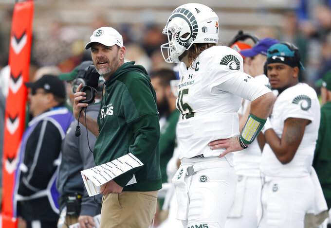 Colorado State head coach Mike Bobo, left, confers with quarterback Collin Hill in the first half of an NCAA college football game against Air Force Thursday, Nov. 22, 2018, at Air Force Academy, Colo. (AP Photo/David Zalubowski)