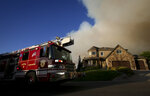 In this Thursday, Sept. 13, 2018, photo a Provo fire engine drives up High Sierra Drive South in Elk Ridge, Utah during a mandatory evacuation. A fast-moving Utah wildfire fanned by high-winds has more than doubled in size as it burns through dry terrain and forces evacuations of hundreds of homes, the U.S. Forest Service said Friday. (Isaac Hale/The Daily Herald via AP)