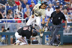 Louisville's Justin Lavey (16) steals third base as Vanderbilt third baseman Austin Martin, top, leaps in an attempt to catch the throw during the seventh inning of an NCAA College World Series baseball game in Omaha, Neb., Friday, June 21, 2019. Lavey went on to score on the throwing error. (AP Photo/Nati Harnik)