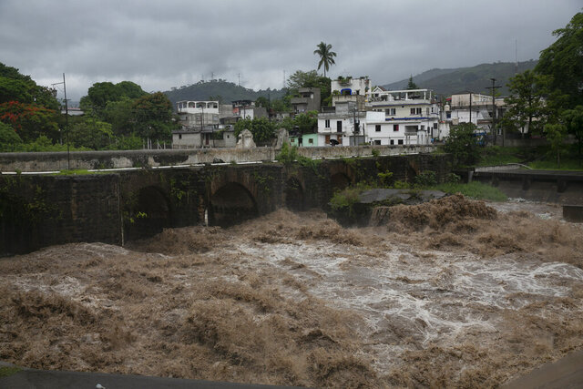 The swollen Los Esclavos River flows violently during tropical storm Amanda in Cuilapa, eastern Guatemala, Sunday, May 31, 2020. The first tropical storm of the Eastern Pacific season drenched parts of Central America on Sunday and officials in El Salvador said at least seven people had died in the flooding. (AP Photo/Moises Castillo)