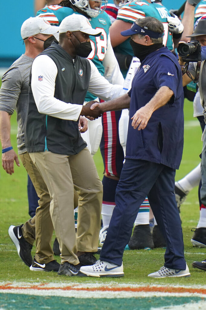 New England Patriots head coach Bill Belichick, right, greets Miami Dolphins head coach Brian Flores at the end of an NFL football game, Sunday, Dec. 20, 2020, in Miami Gardens, Fla. The Dolphins defeated the Patriots 22-12. (AP Photo/Chris O'Meara)