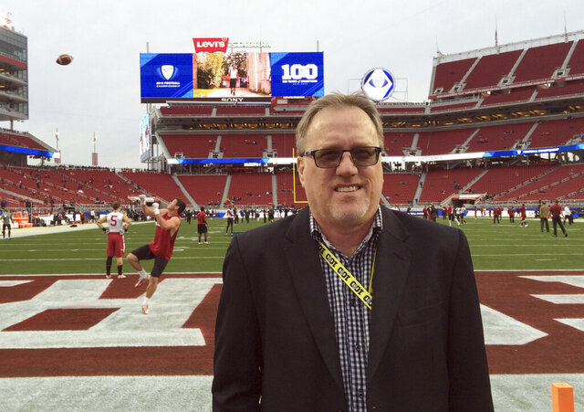 In this Dec. 5, 2015 photo, Los Angeles Times sportswriter, Chris Dufresne poses near the end zone before the Pac-12 championship NCAA college football game in Santa Clara, Calif. Dufresne, an award-winning former sports writer for the Los Angeles Times, died suddenly Monday while dining with his family at home in Chino Hills, 30 miles east of Los Angeles, according to a Times staff memo posted Tuesday, May 26, 2020, on Facebook. He was 62. (Gary Klein/Los Angeles Times via AP)