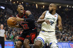 Chicago Bulls' Kris Dunn (32) drives to the basket against Milwaukee Bucks' Khris Middleton during the first half of an NBA basketball game Monday, Jan. 20, 2020, in Milwaukee. (AP Photo/Aaron Gash)