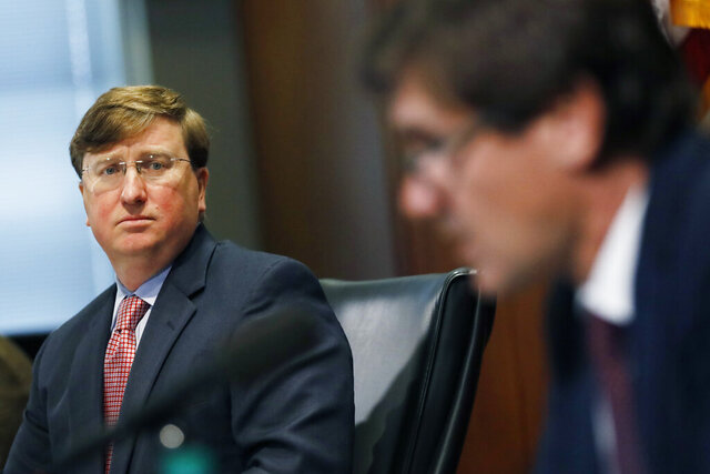 Mississippi Gov. Tate Reeves, left, listens as State Health Officer Dr. Thomas Dobbs, discusses the state's efforts to reduce and limit transmission from the COVID-19 virus, Monday, July 20, 2020, during a press briefing in Jackson, Miss. (AP Photo/Rogelio V. Solis)