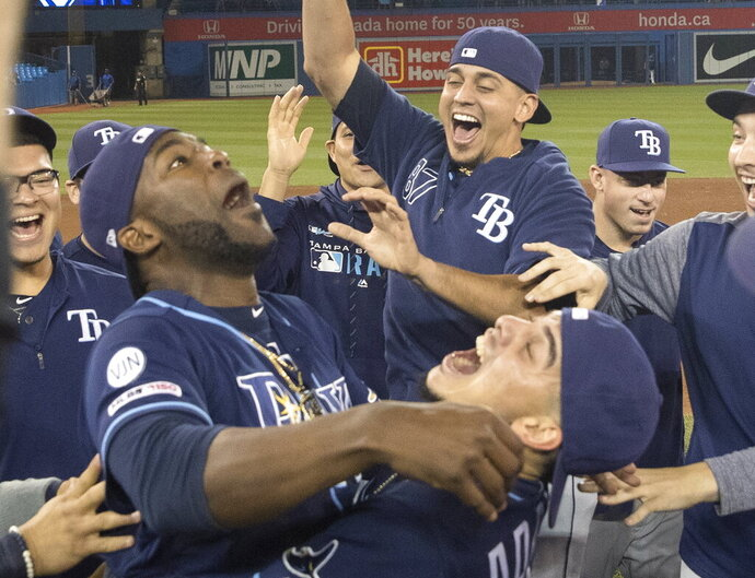 Tampa Bay Rays players celebrate on the field after they defeated the Toronto Blue Jays and clinched an MLB American League wild-card berth in Toronto, Friday, Sept. 27, 2019. (Fred Thornhill/The Canadian Press via AP)
