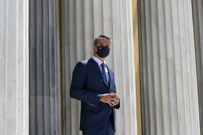 Greece's Prime Minister Kyriakos Mitsotakis waits to welcome the leaders of Cyprus and Jordan ahead of a meeting, in Athens, on Wednesday, July 28, 2021.  Greece is hosting a one-day trilateral meeting of the three leaders.  (AP Photo/Yorgos Karahalis)
