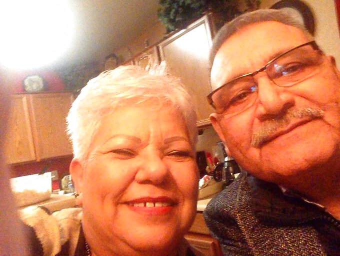 This photo provided by the family shows Carlos Manuel Sandoval with his wife, Rosa, in their kitchen in south Phoenix in the early morning hours of Dec. 25, 2015, after a Christmas Eve celebration with their family. The man known as Don Manuel never stopped hearing the siren call of the sea after he and his family moved to Arizona from their native Guaymas, a port on the southwestern Mexican state of Sonora on the Sea of Cortez. He had three children, nine grandchildren and two great-grandkids. Sandoval died June 30, 2020, from complications of COVID-19 at age 65. (Courtesy of the Sandoval Family via AP)