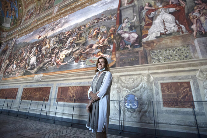 Vatican Museum director Barbara Jatta poses in the Costantino Hall, with frescoes by Italian Renaissance artist Raphael as the Vatican Museum reopened, in Rome, Monday, June 1, 2020. The Vatican Museums reopened Monday to visitors after three months of shutdown following COVID-19 containment measures. (AP Photo/Alessandra Tarantino)