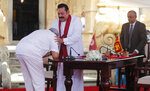 Sri Lanka's former President Mahinda Rajapaksa, center, blesses his younger brother, President Gotabaya Rajapaksa, who pays respect after being sworn in as the prime minister at Kelaniya Royal Buddhist temple in Colombo, Sri Lanka, Sunday, Aug. 9, 2020. (AP Photo/Eranga Jayawardena)