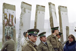 "FILE - In this Nov. 13, 1989, file photo, East German border guards stand in front of segments of the Berlin Wall, which were removed to open the wall at Potsdamer Platz passage in Berlin. Months before the Berlin Wall fell on Nov. 9, 1989, with the Soviet stranglehold over the Eastern Bloc crumbling, a young political scientist named Francis Fukuyama made a declaration that quickly became famous. It was, he declared, ""the end of history."" (AP Photo/John Gaps III, File)"