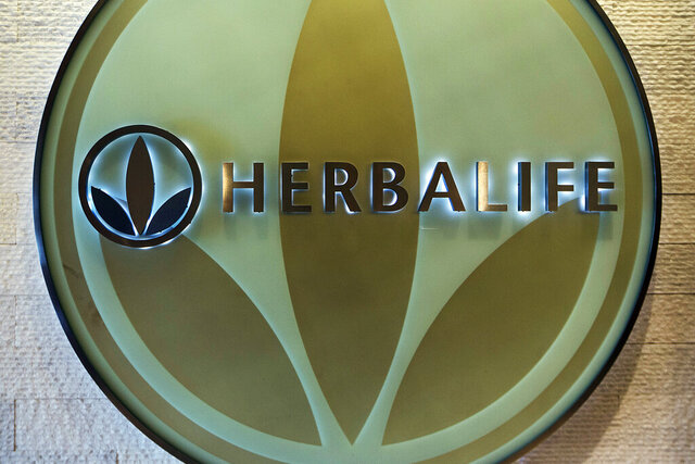 FILE- This May 11, 2016, file photo, shows the Herbalife logo at the company's corporate office in Los Angeles.  The Los Angeles-based health and nutrition company  bribed Chinese government officials for a decade to grow its overseas business and falsified accounting records to cover up the payments, U.S. prosecutors said Friday, Aug. 28, 2020, in announcing corruption charges against the publicly traded company. Herbalife agreed to pay combined penalties of more than $123 million to resolve the charges, federal prosecutors said. (AP Photo/Damian Dovarganes, File)