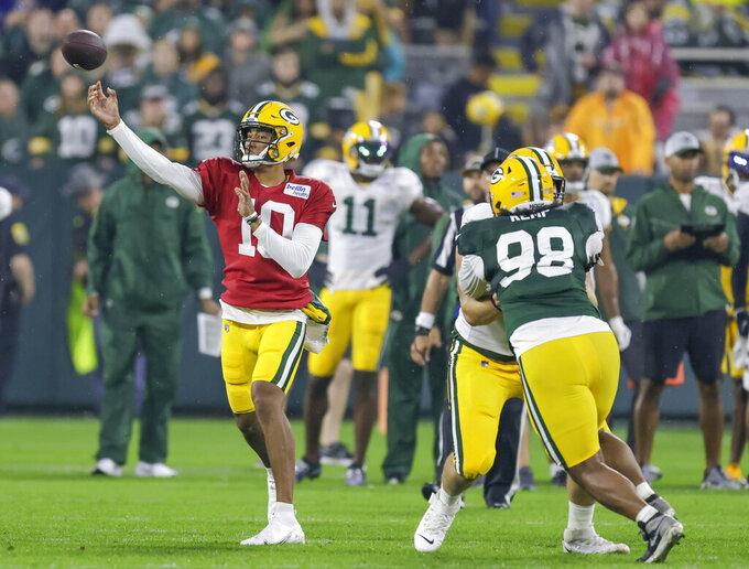 Green Bay Packers quarterback Jordan Love, left, throws a pass during an NFL football training camp at Lambeau Field Saturday, Aug. 7, 2021, in Green Bay, Wis. (AP Photo/Matt Ludtke)