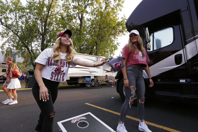 Brooke Bushong, left, throws a cornhole bag as Eloise Bolles looks on before an NCAA college football game between Washington State and Utah State, Saturday, Sept. 4, 2021, in Pullman, Wash. (AP Photo/Young Kwak)