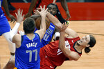 Houston Rockets forward Kelly Olynyk (41) falls while vying for a rebound with Dallas Mavericks guard Luka Doncic (77) and forward Tim Hardaway Jr. (11) during the second half of an NBA basketball game Wednesday, April 7, 2021, in Houston. (AP Photo/Michael Wyke, Pool)