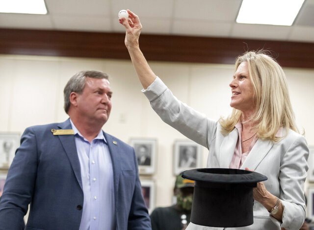 Outgoing Dickinson, Texas mayor Julie Masters, right, holds up a ping-pong ball bearing the name of Sean Skipworth at Dickinson City Hall on Thursday, Jan. 7, 2021. The drawing settled a tie between Dickinson mayoral candidates Jennifer Lawrence and Sean Skipworth. (Stuart Villanueva/The Galveston County Daily News via AP)