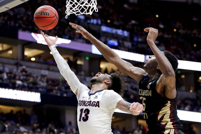 Gonzaga guard Josh Perkins, left, drives to the basket past Florida State forward Mfiondu Kabengele during the first half an NCAA men's college basketball tournament West Region semifinal Thursday, March 28, 2019, in Anaheim, Calif. (AP Photo/Jae C. Hong)
