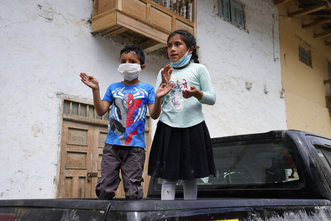 Children applaud as presidential candidate Pedro Castillo walks along Tacabamba, Peru, after voting Sunday, June 6, 2021. Peruvians vote Sunday in a presidential run-off election to choose between Castillo, a political novice who until recently was a rural schoolteacher, and Keiko Fujimori, the daughter of jailed ex-President Alberto Fujimori.(AP Photo/Martin Mejia)