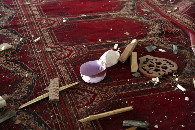 A blood-stained cap is seen inside a mosque after a bomb explosion in Shakar Dara district of Kabul, Afghanistan, Friday, May 14, 2021. A bomb ripped through a mosque in northern Kabul during Friday prayers killing 12 worshippers, Afghan police said. (AP Photo/Rahmat Gul)