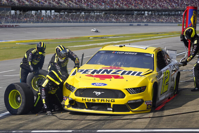 Crew member work to repair damage to Ryan Blaney's car after an incident during the YellaWood 500 NASCAR auto race at Talladega Superspeedway, Sunday, Oct. 4, 2020, in Talladega, Ala. (AP Photo/John Bazemore)