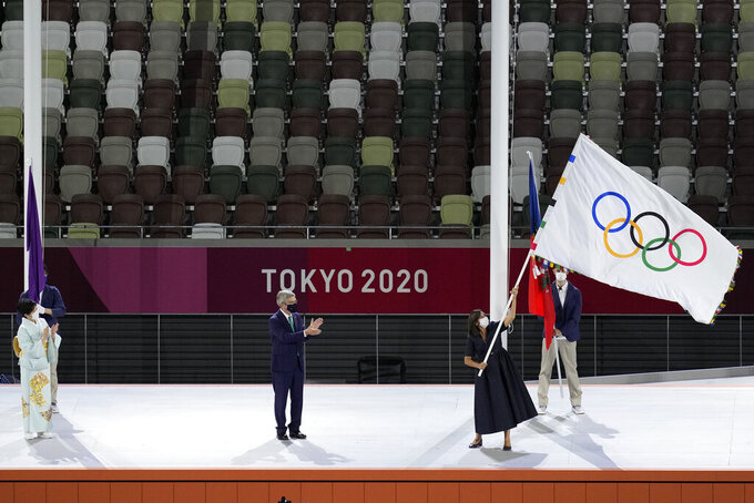 Paris mayor Anne Hidalgo, right, holds the Olympic flag next International Olympic Committee's President Thomas Bach, center, and Tokyo Gov. Yuriko Koike, left, during the closing ceremony in the Olympic Stadium at the 2020 Summer Olympics, Sunday, Aug. 8, 2021, in Tokyo, Japan. (AP Photo/Lee Jin-man)