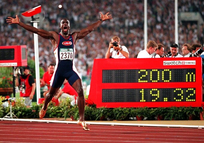 FILE -  In this Aug. 1, 1996, file photo, Michael Johnson, of the United States, celebrates after he won the men's 200 meter final in a world record time of 19.32 at the 1996 Summer Olympic Games in Atlanta.  (AP Photo/Doug Mills, File)