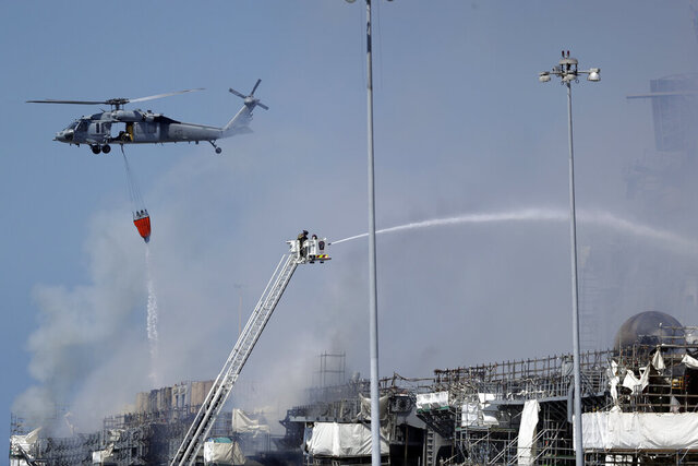 Fire crews battle the fire on the USS Bonhomme Richard, Monday, July 13, 2020, in San Diego. Fire crews continue to battle the blaze Monday after 21 people suffered minor injuries in an explosion and fire Sunday on board the USS Bonhomme Richard at Naval Base San Diego. (AP Photo/Gregory Bull)