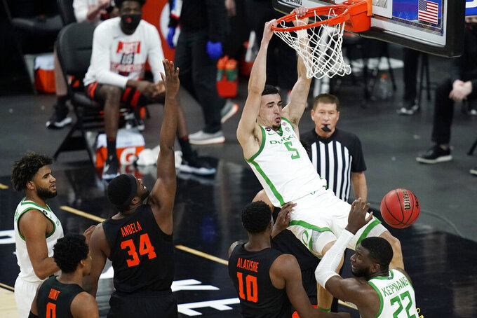Oregon's Chris Duarte (5) dunks against Oregon State during the first half of an NCAA college basketball game in the semifinal round of the Pac-12 men's tournament Friday, March 12, 2021, in Las Vegas. (AP Photo/John Locher)