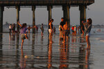 Tourists gather near The Pier early Wednesday, Aug. 5, 2020, at Old Orchard Beach, Maine. Vacationers have returned to the popular seaside town in a state that ranks one of the lowest in the nation in positive cases of coronavirus. (AP Photo/Robert F. Bukaty)