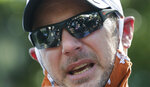 FILE - Texas football players are reflected in the glasses of coach Tom Herman in Austin, Texas, Thursday, June 4, 2020, after they marched to the State Capitol during a protest over the death of George Floyd, who died May 25 after being restrained by police in Minneapolis. Back when everything was still normal in college football, Texas coach Tom Herman did some house cleaning. Tossed out were the offensive and defensive coordinators in favor of new assistants with past connections to Herman and the Big 12. By spring, four more new assistants were on staff.  Such a major rebuild after a disappointing 8-5 finish in 2019 would typically raise the temperature on a fourth-year coach who is 25-15 with the Longhorns and paid $6.2 million in expectation that No. 14 Texas will soon return to a Big 12 championship not won in more than a decade.(AP Photo/Eric Gay, File)