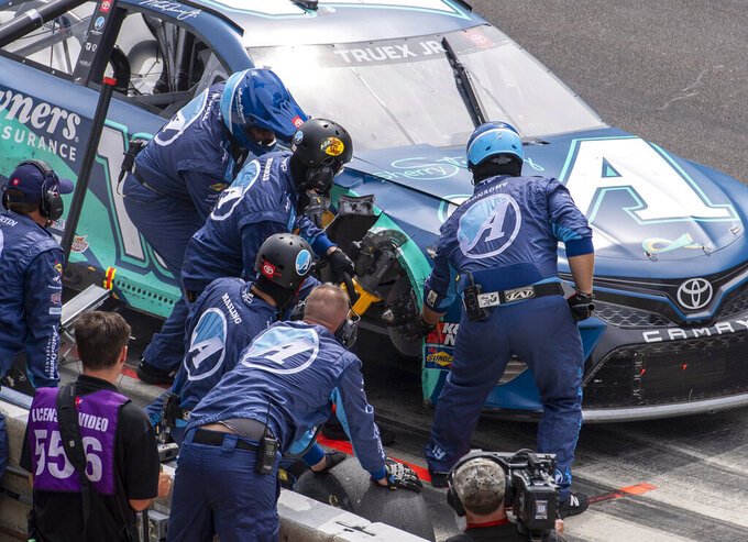 The pit crew of Martin Truex Jr. (19) work to cut away part of the car's fender during a NASCAR Cup Series auto race at Indianapolis Motor Speedway, Sunday, Aug. 15, 2021, in Indianapolis. (AP Photo/Doug McSchooler)