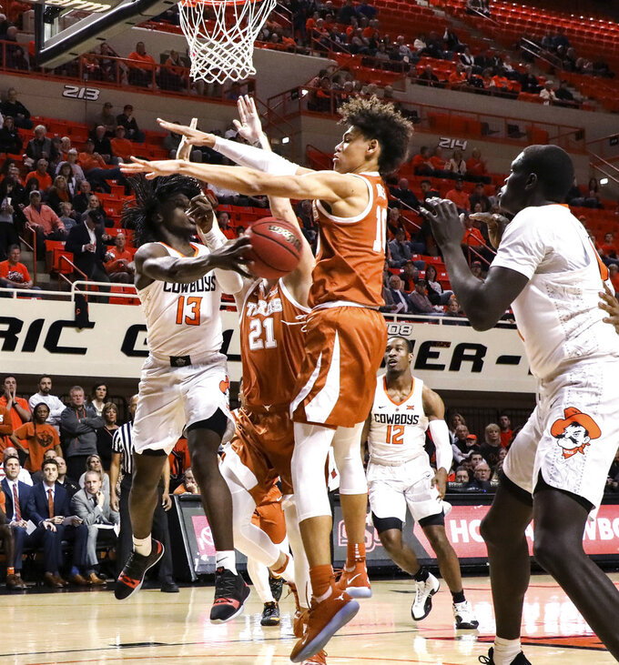 Oklahoma State's Isaac Likekele passes the ball to teammate Yor Anei during the first half of the team's NCAA college basketball game against Texas on Tuesday, Jan. 8, 2019, in Stillwater, Okla. (Evan Brown/Tulsa World via AP)