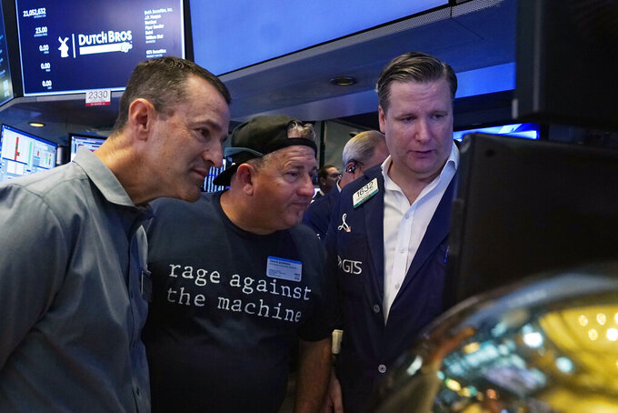 President and CEO of Dutch Bros Coffee Joth Ricci, left, and Travis Boersma, center, co-Founder and President, meet with specialist Gregg Maloney on the floor of the New York Stock Exchange, before their IPO, Wednesday, Sept. 15, 2021. (AP Photo/Richard Drew)