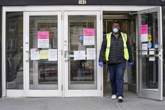 A worker leaves the the Frank P. Zeidler Municipal Building Monday March 30, 2020, in Milwaukee. The city is now allowing drive up early voting for the state's April 7 election. (AP Photo/Morry Gash)
