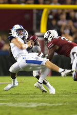 Kentucky quarterback Will Levis, front left, takes a hit by South Carolina defensive lineman Jabari Ellis (99) and defensive end Jordan Burch (3) in the first half of an NCAA college football game Saturday, Sept. 25, 2021, at Williams-Brice Stadium in Columbia, S.C. (AP Photo/Hakim Wright Sr.)