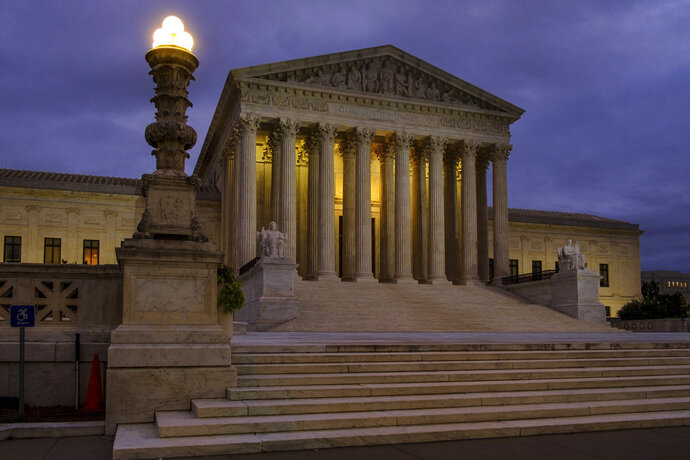 """In this Oct. 5, 2018 photo the U. S. Supreme Court building stands quietly before dawn in Washington.  A couple of liberal Harvard law professors are lending their name to a new campaign that wants to build support for expanding the Supreme Court by four justices. The campaign being launched Wednesday also wants to increase the size of the lower federal courts to counteract what it terms """"Republican obstruction, theft and procedural abuse"""" of the federal judiciary.   (AP Photo/J. David Ake)"""