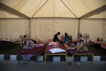Migrant workers rest inside a tent before traveling in a Shramik train arranged to transport them to their home states, at a railway station in Gauhati, India, Thursday, May 28, 2020. Rural villages across India are seeing an increase in cases with the return of hundreds of thousands of migrant workers who left cities and towns where they were abandoned by their employers after having toiled for years building homes and roads. India sees no respite from the coronavirus caseload at a time when the two-month-old lockdown across the country is set to end on Sunday. (AP Photo/Anupam Nath)