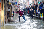 A woman tries to cross a flooded street as people walk on a trestle bridge during high water, in Venice, northern Italy, Friday, Nov. 15, 2019. Exceptionally high tidal waters returned to Venice on Friday, prompting the mayor to close the iconic St. Mark's Square and call for donations to repair the Italian lagoon city just three days after it experienced its worst flooding in 50 years. (Andrea Merola/ANSA via AP)