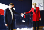Candidate in Poland's tight presidential election runoff, incumbent President Andrzej Duda and First Lady Agata Kornhauser-Duda cast their ballots at a polling station in their hometown of Krakow, Poland, on Sunday, July 12, 2020. Conservative Duda is running against liberal Warsaw Mayor Rafal Trzaskowski and latest opinion polls suggest the race will be decided by a very narrow margin.(AP Photo/Czarek Sokolowski)