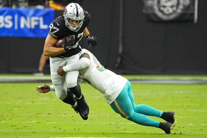 Las Vegas Raiders tight end Foster Moreau (87) runs for a gain against Miami Dolphins outside linebacker Jerome Baker (55) during the first half of an NFL football game, Sunday, Sept. 26, 2021, in Las Vegas. (AP Photo/Rick Scuteri)