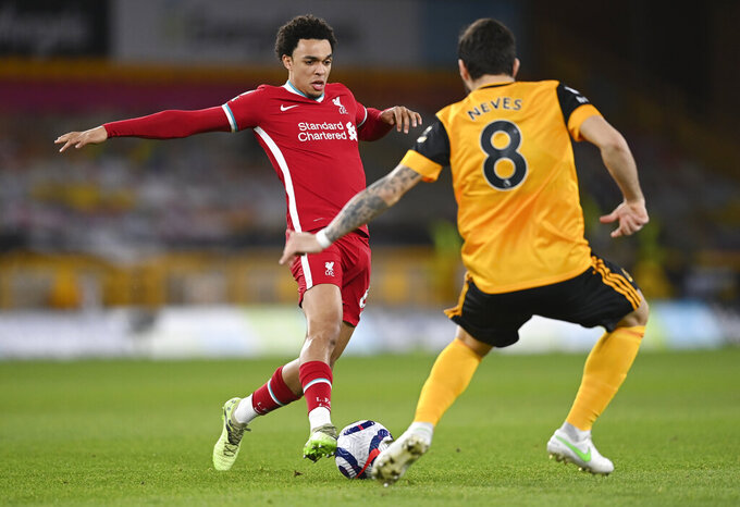 Liverpool's Trent Alexander-Arnold, left, takes the ball past Wolverhampton Wanderers' Ruben Neves during the English Premier League soccer match between Wolverhampton Wanderers and Liverpool at Molineux Stadium in Wolverhampton, England, Monday, March. 15, 2021. (AP Photo/Laurence Griffiths,Pool)