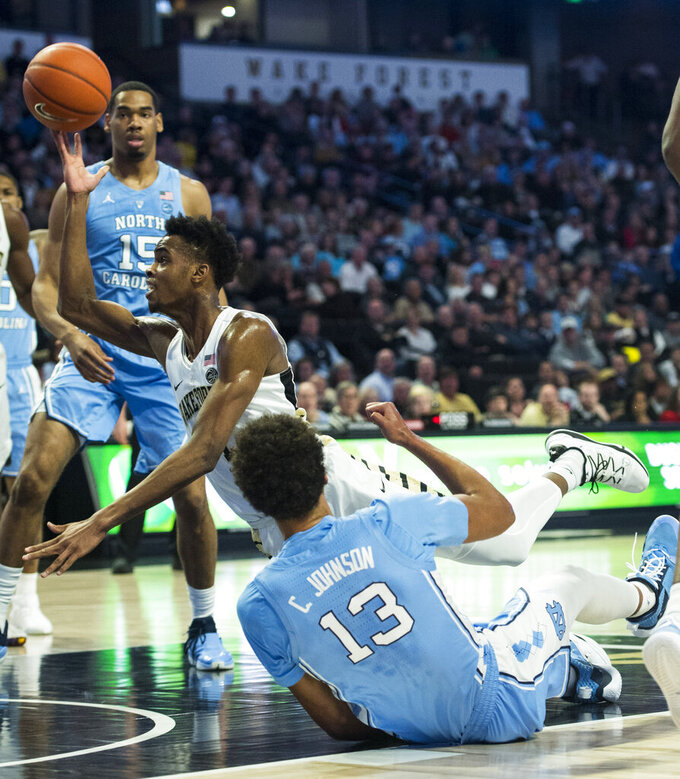 Wake Forest's Isaiah Muius (1) falls to the floor after colliding with North Carolina's Cameron Johnson (4) during the first half of an NCAA college basketball game in Winston-Salem, N.C., on Saturday, Feb 16, 2019. (AP Photo/Woody Marshall)