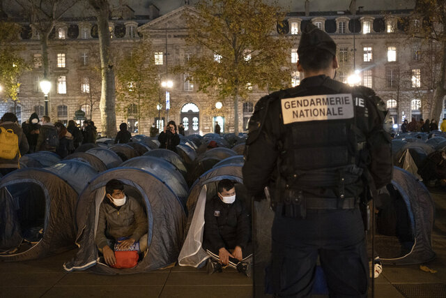 A police officer stands in front of migrants in a makeshift camp set up Monday night Nov.23, 2020 on Place de la Republique in Paris. Paris police are under government orders to explain themselves after officers were filmed tossing migrants out of tents while evacuating a makeshift camp in the French capital. (Alexandra Henry/Utopia56 via AP)