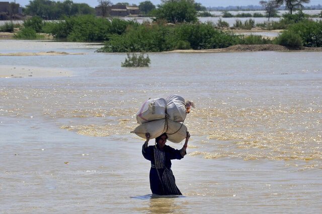 A woman carries sack of wheat and household goods while she wades through a flooded area of Dadu, a district in Pakistan's southern Sindh province, Sunday, Aug. 9, 2020. Three days of heavy monsoon rains triggering flash floods killed at least dozens people in various parts of Pakistan, as troops with boats rushed to a flood-affected district in the country's southern Sindh province Sunday to evacuate people to safer places. (AP Photo/Pervez Masih)